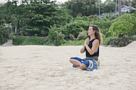 Woman practicing yoga on the beach - MOMF00162