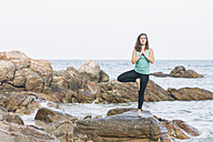 Woman practicing yoga on a rock at the sea - MOMF00165
