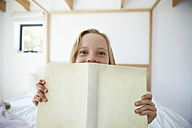 Portrait of little girl with book at home - SRYF00255