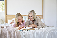 Little girl lying on the bed with her grandmother reading a book - SRYF00270