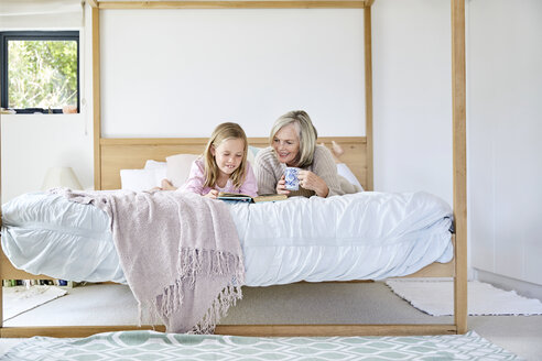 Little girl lying on the bed with her grandmother reading a book - SRYF00273