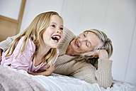 Portrait of laughing little girl lying on the bed with her grandmother - SRYF00279