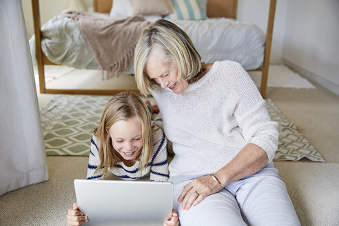 Little girl and her grandmother using tablet at home - SRYF00294