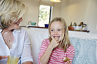 Portrait of smiling little girl eating sandwich while grandmother watching her - SRYF00300