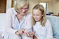 Grandmother and granddaughter sitting on the couch at home looking at smartphone - SRYF00303