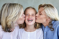 Portrait of happy little girl kissed by mother and grandmother - SRYF00318