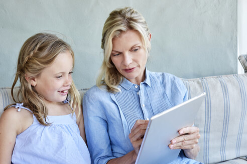 Mother and little daughter sitting together on couch looking at tablet - SRYF00336
