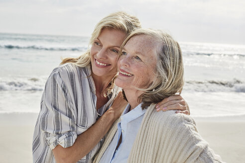 Senior woman and her adult daughter standing on the beach, embracing - SRYF00345