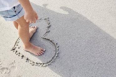 Little girl standing barefoot in a heart on sand - SRYF00351