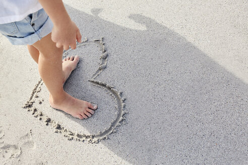 Little girl standing barefoot in a heart on sand - SRYF00351