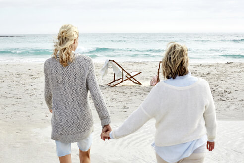 Mother and daughter walking on the beach, holding hands - SRYF00372