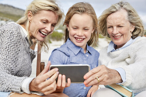Mother, daughter and grandmother taking smartphone selfies on the beach - SRYF00375