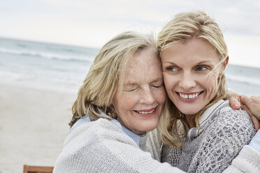 Mother and daughter embracing on the beach - SRYF00387