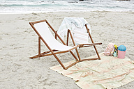 Empty sun loungers on the beach with towels and toys - SRYF00390