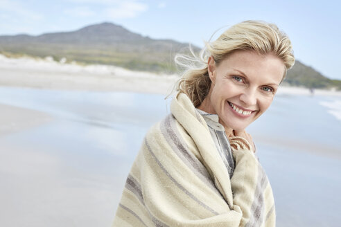 Mature woman enjoying the sea, wrapped in a blanket - SRYF00396