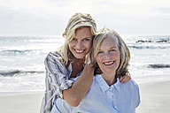 Mother and daughter embracing by the sea - SRYF00426