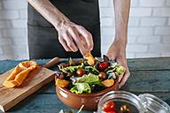 Man preparing batavia lettuce salad,  partial view - KIJF01420