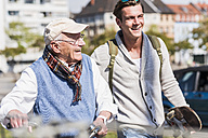 Happy senior man with adult grandson in the city on the move - UUF10415