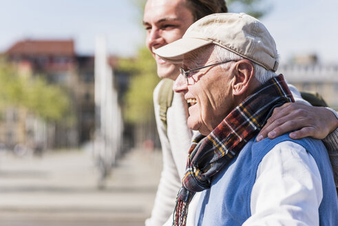 Happy senior man with adult grandson in the city - UUF10421