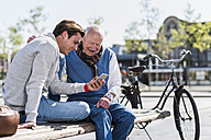 Senior man and adult grandson on a bench looking at cell phone - UUF10427
