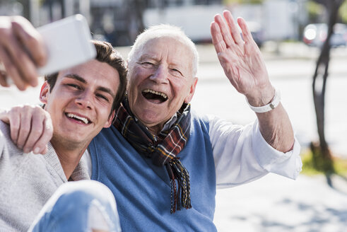 Happy senior man and adult grandson taking a selfie - UUF10430