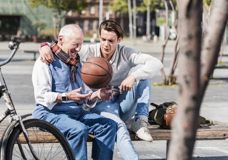 Senior man and adult grandson with basketball talking on a bench - UUF10433