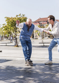 Adult grandson assisting senior man on skateboard - UUF10436
