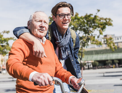 Senior man with adult grandson in the city on the move - UUF10439