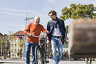 Happy senior man with adult grandson in the city on the move - UUF10442