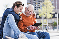Happy senior man and adult grandson looking at tablet - UUF10454