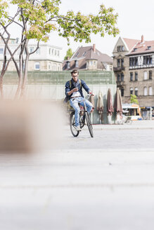 Young man with bicycle in the city using cell phone - UUF10463