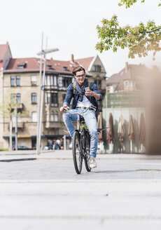 Smiling young man with bicycle in the city looking at cell phone - UUF10466