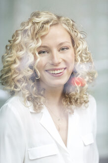 Portrait of smiling blond businesswoman behind windowpane - PESF00520