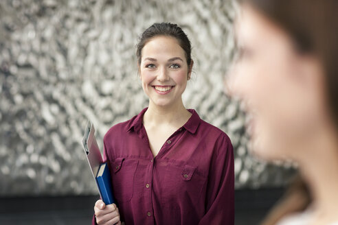 Portrait of smiling young businesswoman with notebook and clip board - PESF00535