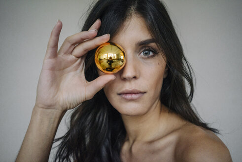 Portrait of attractive dark-haired young woman holding Christmas bauble - KNSF01221