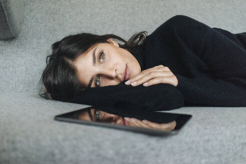 Serious young woman lying on couch next to tablet - KNSF01224