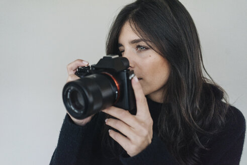 Dark-haired young woman holding a camera - KNSF01236