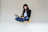 Smiling young businesswoman sitting on chair using laptop - KNSF01245