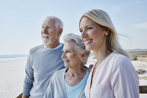 Smiling senior couple with adult daughter on the beach - RORF00758