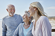 Happy senior couple with adult daughter on the beach - RORF00761