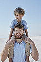 Portrait of father carrying son piggyback on the beach - RORF00764