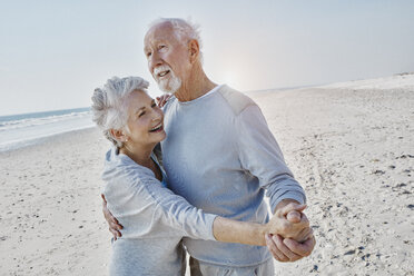 Happy senior couple dancing on the beach - RORF00779