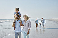 Happy extended family strolling on the beach - RORF00788