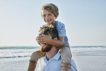 Father carrying son piggyback on the beach, son covering father's eyes - RORF00791