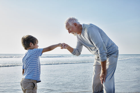 Grandfather giving grandson a fist bump on the beach - RORF00794