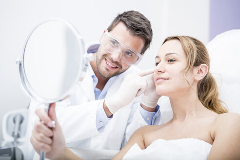 Aesthetic surgery, woman looking in mirror - WESTF22978