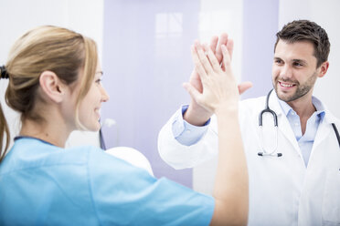 Two smiling doctors high fiving - WESTF22987