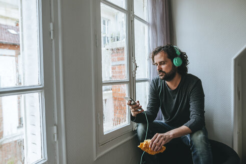 Man listening music with headphones and smartphone at home - KIJF01440