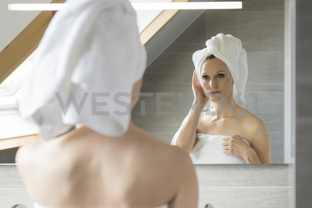 Woman looking at her mirror image in the bathroom - CHPF00394