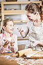 Mother and daughter baking bread in kitchen together - WESTF22993